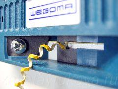 WEGOMA AU-93 в процессе обрезки меламиновой кромки. Крупный план.